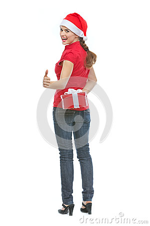 Happy young woman hiding Christmas present box