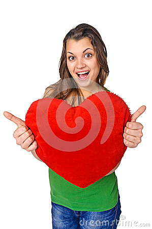 Happy young woman holding red heart shaped pillow