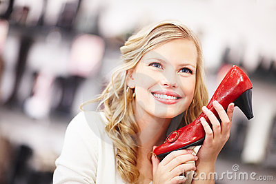 Happy young woman holding a red shoe