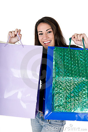 Happy young woman holding shopping bags, isolated