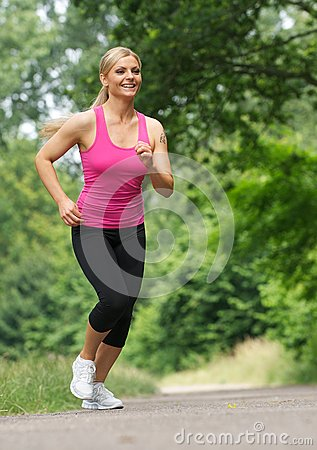 Happy young woman jogging outdoors