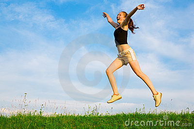 Happy young woman is jumping on green grass