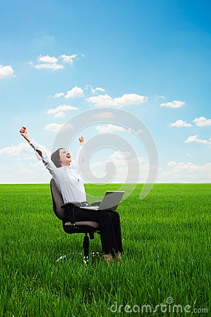 Happy young woman with laptop on the meadow