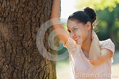 Happy young woman lean against tree