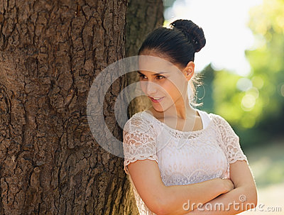 Happy young woman lean against tree in park
