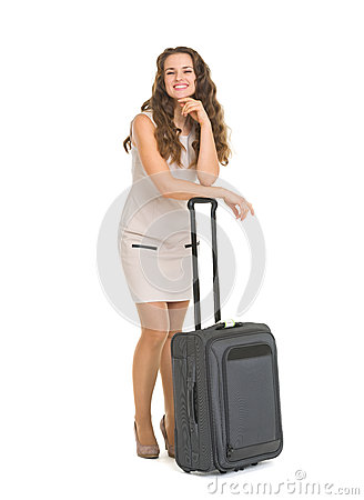 Happy young woman leaning on wheels suitcase