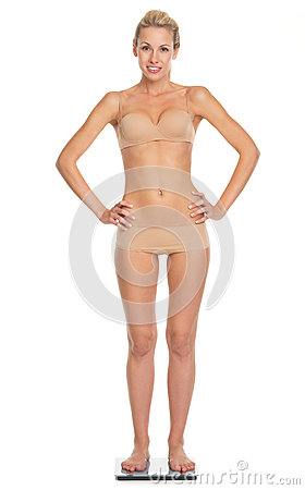 Happy young woman in lingerie standing scales Stock Photo