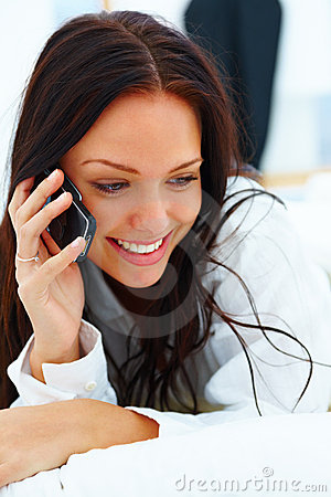 Happy young woman lying talking on mobile phone