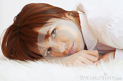 Happy young woman lying on white fur plaid
