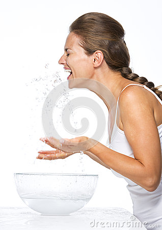 Happy young woman making water splashes while washing face