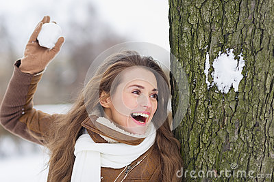 Happy young woman playing in snowball fights