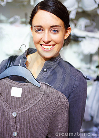 Happy young woman purchasing clothes in store