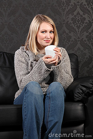 Happy young woman relaxed at home drinking coffee