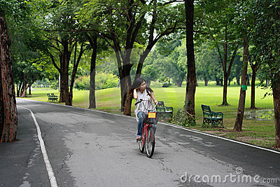 Happy young woman relaxing over bicycle