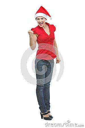 Happy young woman in Santa hat rejoicing success