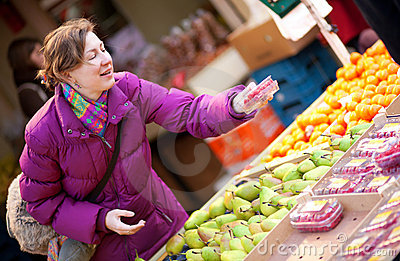Happy young woman selecting fruits
