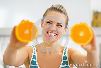 Happy young woman showing slices of orange