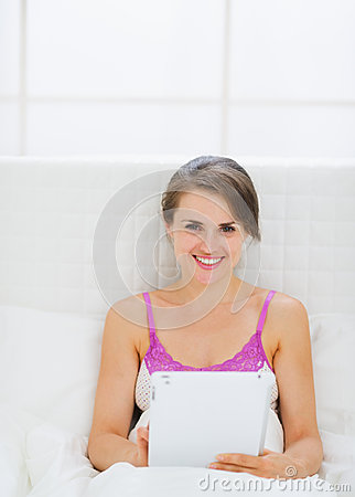 Happy young woman sitting on bed with tablet PC