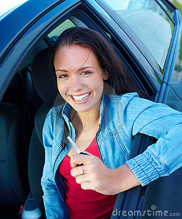 Happy young woman sitting in a car and holding key