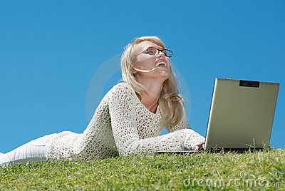 Happy young woman smiling and working on a laptop