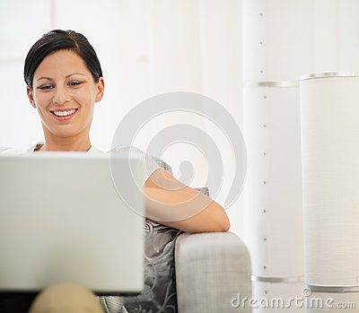 Happy young woman surfing net on laptop