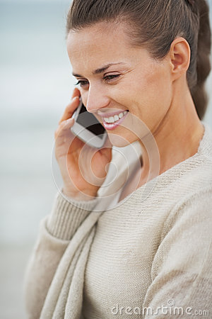 Happy young woman in sweater on beach talking cell phone