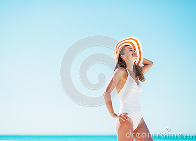 Happy young woman in swimsuit and beach hat relaxing on beach