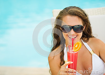 Happy young woman in swimsuit drinking cocktail