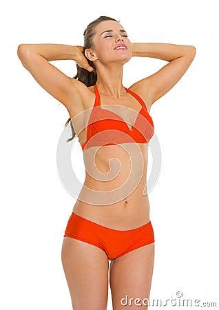 Happy young woman in swimsuit enjoying sunbathing