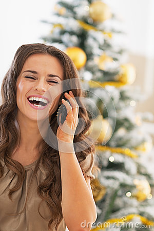 Free Happy Young Woman Talking Cell Phone Near Christmas Tree Royalty Free Stock Photos - 35700938
