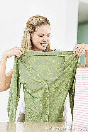 Happy young woman trying her new green top