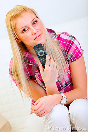Happy young woman with TV remote control