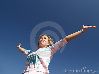 Happy young woman under blue sky