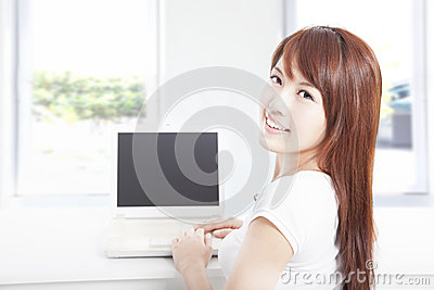 Happy young woman using the laptop at home