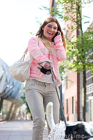 Happy young woman walking her dog in the city and talking on the phone