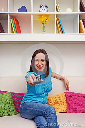Happy young woman watching tv