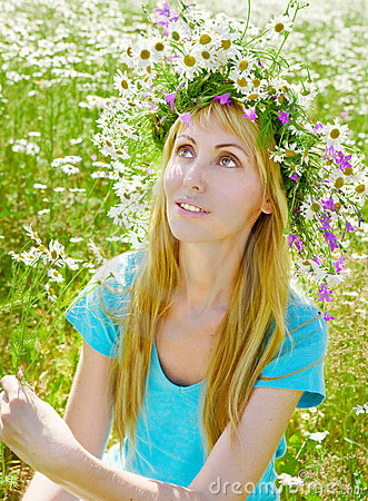 The happy young woman in a wreath from wild flower