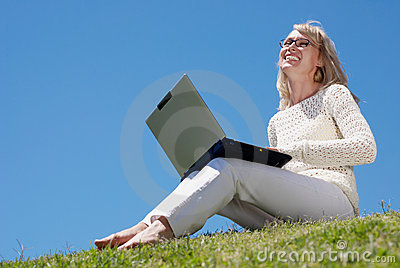 Happy young women smiling and working on a laptop