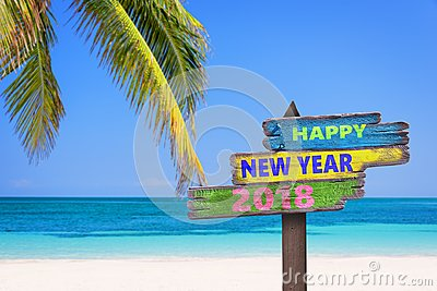 Hapy new year 2018 on a colored wooden direction signs, beach and palm tree Stock Photo