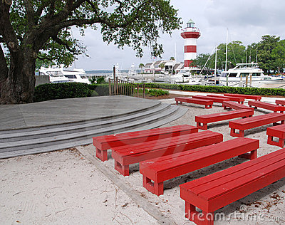 Harbor town lighthouse with red benches on Hilton