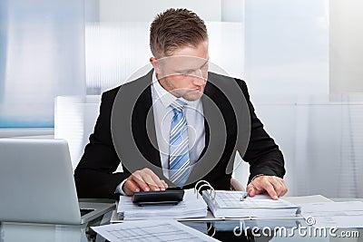 Hardworking Businessman Analyzing A Report Stock Photo ...