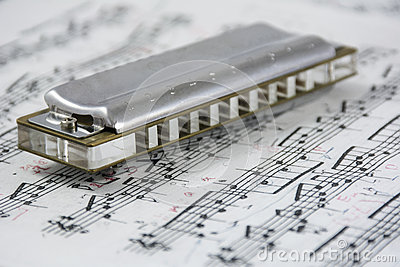 Harmonica is on the musical notes Stock Photo