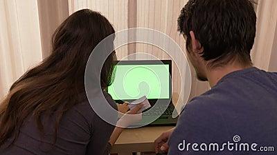 Hartelijk jong paar die online van huis winkelen die laptop met het groene scherm met behulp van stock footage