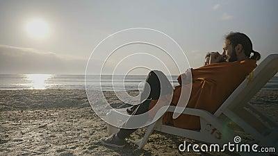 Hartelijk jong paar die op een zitkamerstoel liggen op het strand die op de zonsondergang letten terwijl wordt behandeld met een  stock footage