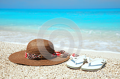 Hat and flip-flops on a beach