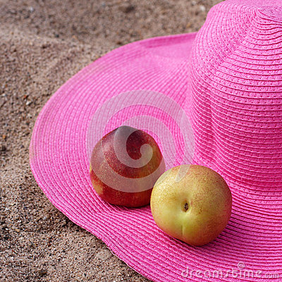 Hat and nectarines on the sand