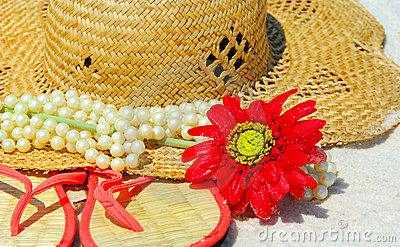 Hat, Sandals and pearls on beach