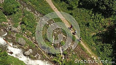 Haut de la page sentier de randonnée rocheuse et ruisseau de montagne rapide trois touristes banque de vidéos