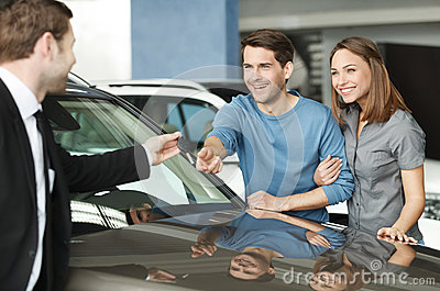 They have made a right vehical choise. Young car salesman giving