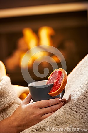 Having hot tea in front of fireplace